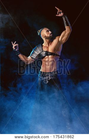 Young and muscular man performing a theatrical pose on stage. Striptease. Handsome man