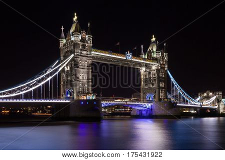 Tower Bridge with reflections in the Thames river at night, London, UK