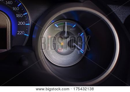 Dashboard of a car fuel gauge and low fuel signal.