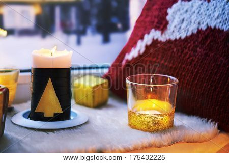 candles and pillow with xmas decoration on windowsill. winer mood