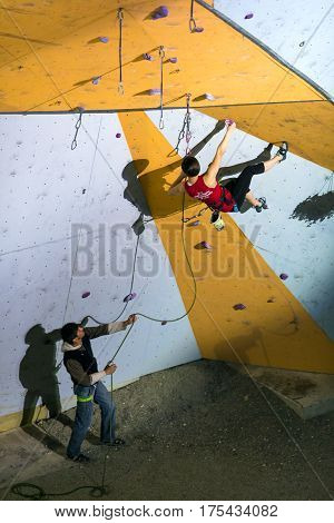 Elegant female Climber climbing wall, belaying Referee holding Rope. National Climbing Championship, Lead Finals, Dnipro, Ukraine, May 21, 2016