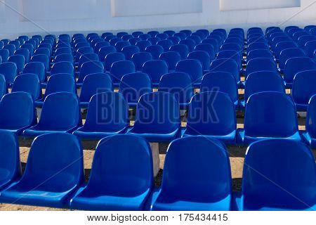 close-up of a few rows of empty plastic chairs at the stadium
