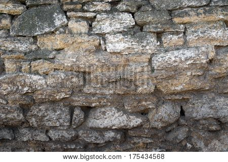 old stone wall made of stone in lime has slipped