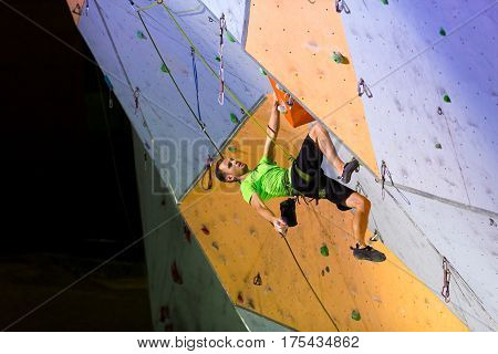 Male Climber hanging on Climbing Wall. National Climbing Championship, Lead climbing Finals, Dnipro, Ukraine, May 21, 2016