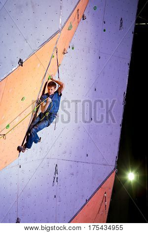 Male Climber trying fix a rope on Climbing Wall. National Climbing Championship, Lead climbing Finals, Dnipro, Ukraine, May 21, 2016