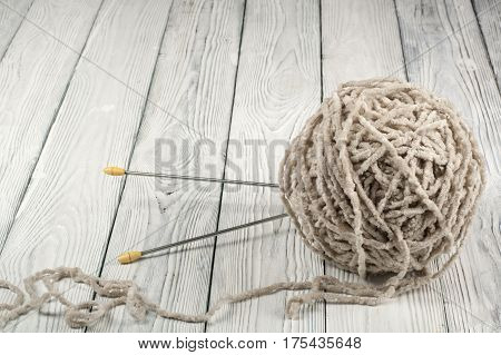 Ball of wool with spokes for handmade knitting on wooden table. Knitting wool and knitting needles