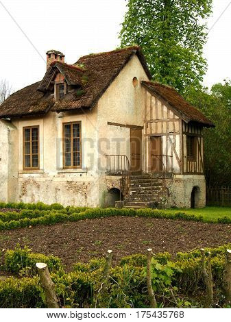 A traditional French cottage with a small garden and a thatched roof.