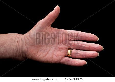 Mature Woman's Hand In Greeting Gesture. On Black.