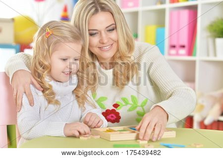 mother with little daughter counting with sticks