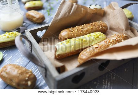 Eclairs with chocolate and whipped cream on dark background. Traditional French dessert. Top view.