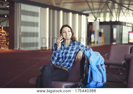 Woman passenger at the waiting area resting and waiting for her flight