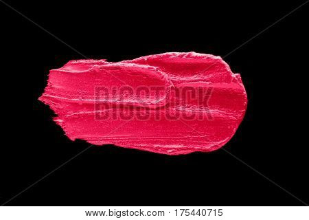 Pink lipstick smudged on a black isolated background