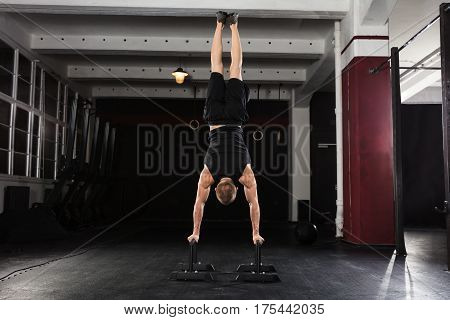 Young Athlete Man Doing Handstand Exercise On Parallel Bar In The Gym