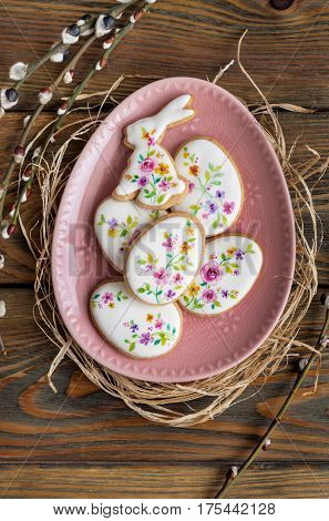 Colorful Easter cookies on wooden background. Floral icing decorated cookies.