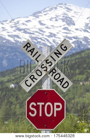 The railroad crossing sign on a gold rush railway outside Skagway town (Alaska).