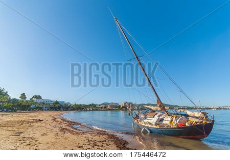 Abandoned & stranded, rusty old sail boat on the beach in Sant Antoni De Portmany. Warm sunny day in Balearic Islands, Spain.