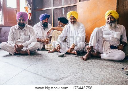 Amritsar, India - August 15, 2016: Sikhs men siting in the  free canteen in Golden Temple, Amritsar, India