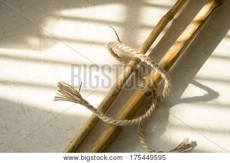 Bamboo canes composition on a marble surface. Natural lighting from the window