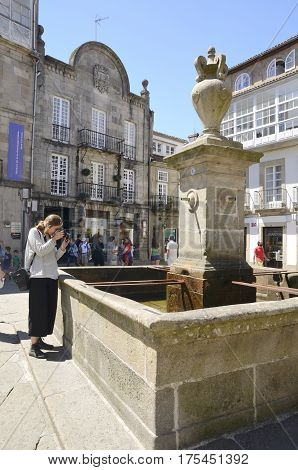SANTIAGO DE COMPOSTELA, SPAIN - AUGUST 5, 2016: Young woman taking a photo of a fountain in a plaza of the old town of the city in Santiago de Compostela Galicia Spain