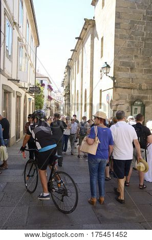 SANTIAGO DE COMPOSTELA, SPAIN - AUGUST 5, 2016: Cyclist and people on street in the old town of the city in Santiago de Compostela Galicia Spain