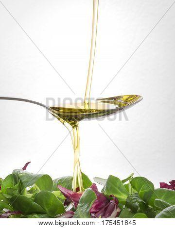 Vertido de Aceite oliva virgen en cuchara con ensalada