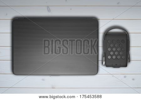 A closed laptop and an external hard drive lie on a light wooden background. View from above