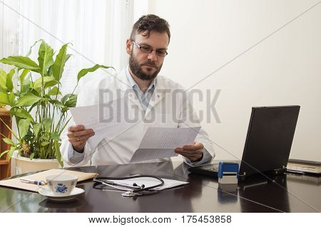 A doctor in a white coat in a doctor's office sits at a table and fills papers Doctor's office.