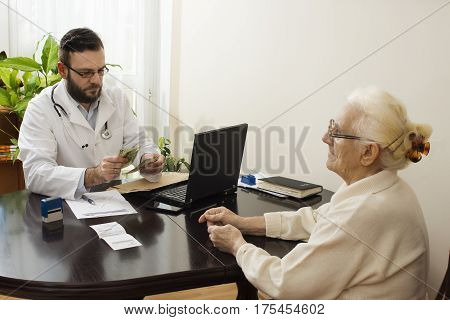 The doctor collects a fee from an old lady in a private doctor's office. Doctor counts money received from patient.