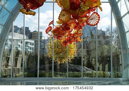 SEATTLE-DEC 1, 2014: View of the Space Needle from inside the Chihuly Garden and Glass museum conservatory next door. Unique perspective. Reflections. Focus is on the glass sculpture in the foreground.