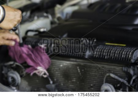 Blurry image Man was cleaning and wiping car radiator fin and car engine with Hand and Violet Microfiber Cloth and Air gun. Air pressure Car cleaning Car Washing