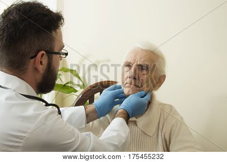 The doctor examines the lymph nodes on the neck of an old woman. The doctor geriatrician during the test.