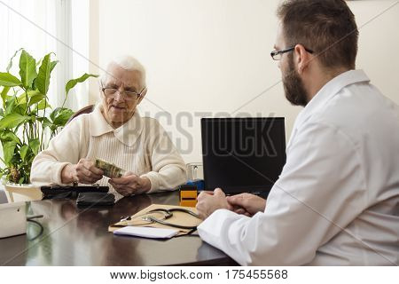 The old grandmother deducts the money in the doctor's office. Grandma pays the doctor for a visit to a private doctor's office.
