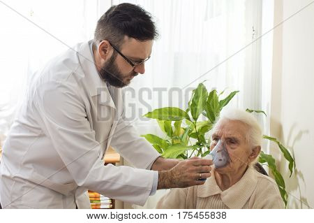 Inhalation of the upper respiratory tract.  The doctor's office conducted inhalation.  The old woman during inhaltion. The patient keeps inhaler.