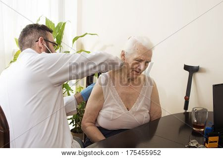 Doctor examining an old woman with a stethoscope in a doctor's office. Medical examination with a stethoscope. Geriatrician doctor examining lungs.