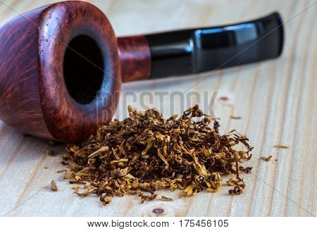 Dose of dry Tobacco and stylish Vintage Pipe on wooden Background