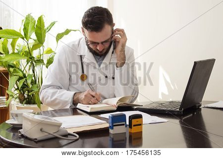 Doctor in the doctor's office talking on the phone and checks for available dates on the calendar. The doctor during a phone call saves appointment in the calendar.