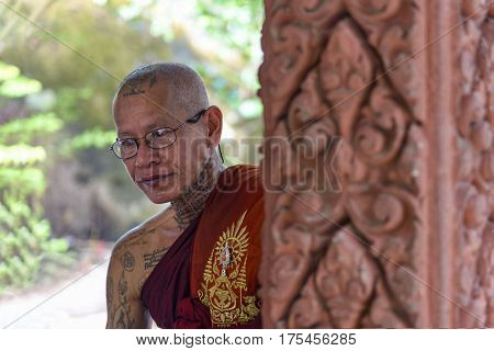 Phnom Kulen, Cambodia - January 03, 2017: Portrait of a tattooed Buddhist monk in traditional robe behind a column of Phnom Kulen pagoda