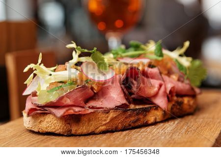 Sandwich with roast beef on restaurant table, close-up