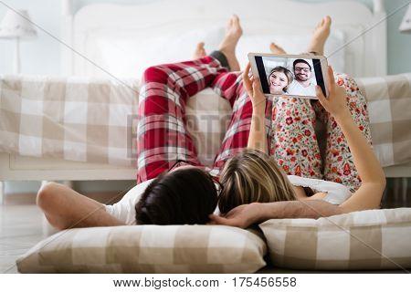 Loving couple taking selfies at home in pajamas