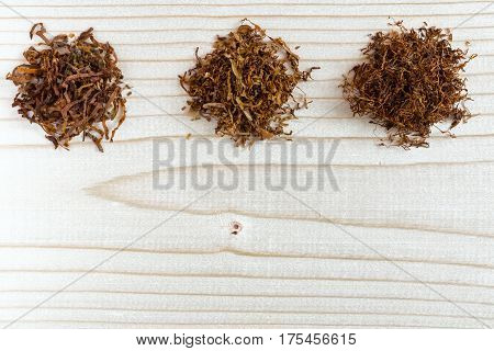 Three different sorts of finer and larger cuts Tobacco for Pipe and handmade Cigarettse on natural wood Background