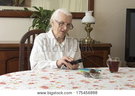 Old woman at the table with remote control for the TV.  The old woman turns on the TV remote control sitting at the table.  The old woman in glasses sitting at the table and looking for the right button on the TV remote control.