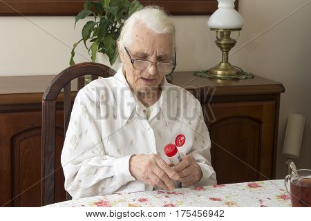 The old woman lubricates the hands creme sitting at the table.  Grandmother sitting at a table in the living room and lubricates hand salve.