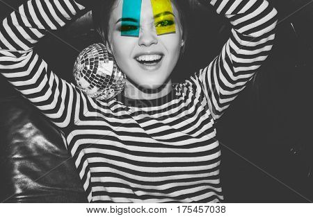 Young attractive emotional girl at party in strip dress holding and looking through colorful camera roll plastic film strips like sunglasses. Smiling woman lie in leather sofa laugh and having fun