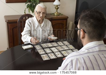 Grandma puts tarot grandson.  Age fairy puts tarot cards  Very old woman puts a man tarot cards.  Fortune-telling with tarot cards.