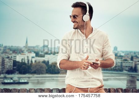 Young man listening to music on a smart phone.He is listening music on smartphone in the city.