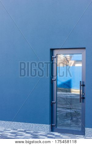 The door tinted glass with a grey frame in the office building. Dark blue wall.