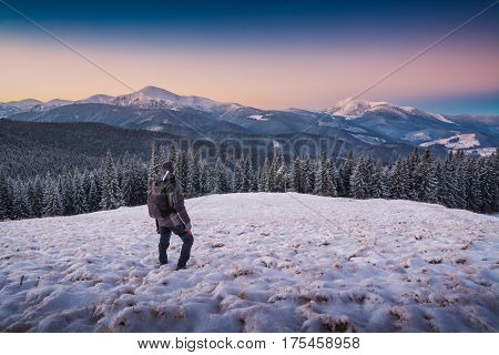 Hiker Standing On A Hill With Snow