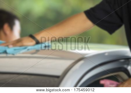 Blurry image Man was wiping car roof with hand and microfiber cloth Car cleaning Car washing