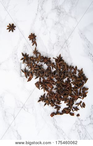 Top view of star anise spice on white marble background