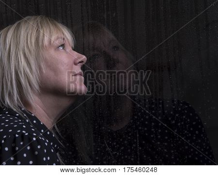 Mature blonde woman indoors looking out of a window splashed with rain
